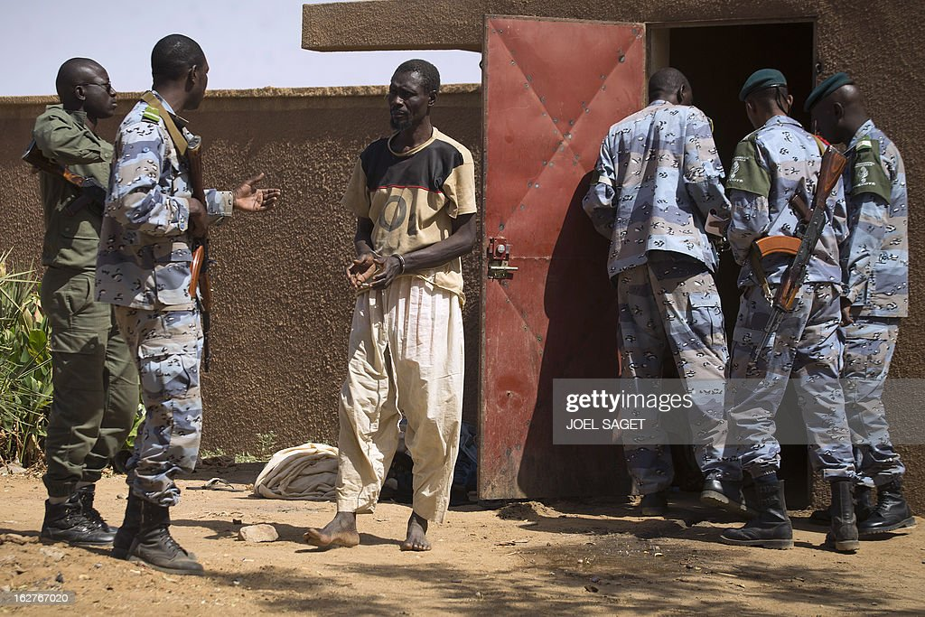 One of nine prisoners, comprising seven Malian, one Nigerois and one Mauritanian, are taken out of a jail at the gendarmerie in the northern Malian city of Gao on February 26, 2013 to be transferred on a military flight to Bamako, where they are to be judged on charges of belonging to the main Islamist armed group, the Movement for Oneness and Jihad in West Africa (MUJAO), an Al-Qaeda offshoot. French and Malian government forces reconquered on January 26 the city opf Gao, two weeks after Paris launched an offensive in the north.