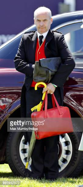 One of Queen Elizabeth II's footmen carries her red briefcase and yellow trimmed umbrella as he accompanies The Queen to Derby Day during the...