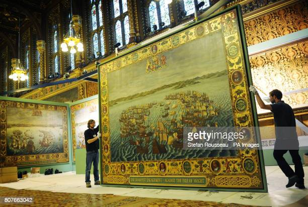 One of six paintings recreating the 'Armada Tapestries' giant gilded canvases depicting the defeat of the Spanish Armada is inched into place in the...