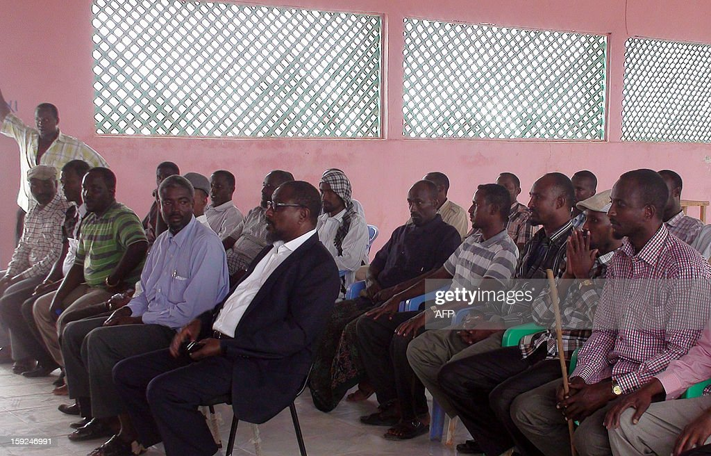 One of Somalia's most notorious pirate leaders, Mohamed Abdi Hassan (C, first row), known as 'Afweyne' or 'Big Mouth', attends a ceremony on January 9, 2013 in the central Somali region of Adado to announce that he was retiring after years of terrorizing the Indian Ocean, generating millions of dollars in ransoms from seized ships. Afweyne did not provide a reason for his decision to quit piracy. AFP PHOTO - Abdi Hussein