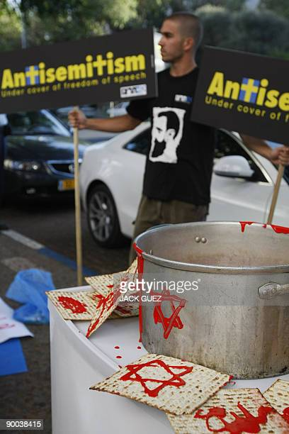One of some 20 Israeli demonstrators holds placards reading 'AntiSemitism under the cover of freedom of expression' during a protest outside the...
