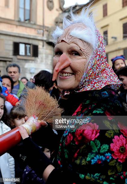 One of the 100 women dressed as the witch Befana carries a 52metre long stocking full of presents during the annual Befana procession in Viterbo on...