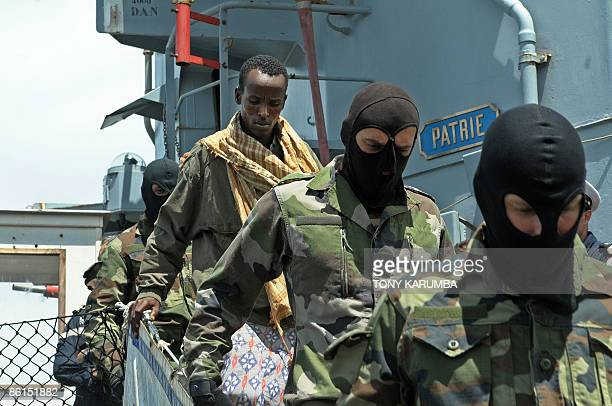 One of the 11 suspected pirates all of whom are Somali nationals is escorted by a masked French marines to be handed over to Kenyan authorities on...