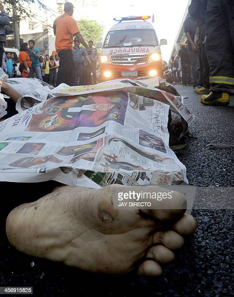 One of the 22 bodies lies on the road beside the crashed bus that fell from an elevated highway in Manila on December 16 2013 Twentytwo people were...