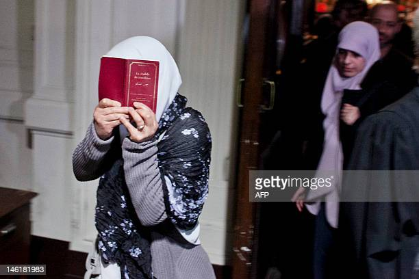 One of the accused hides her face as she leaves the Court of Assizes in Brussels on June 11 after the announcement of the verdict of the trial of...