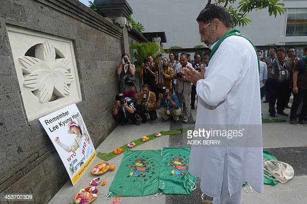 One of the activists from around the world called La Via Campesina Social Movement for an Alternatif Asia prays for late South Korean farmer Lee...