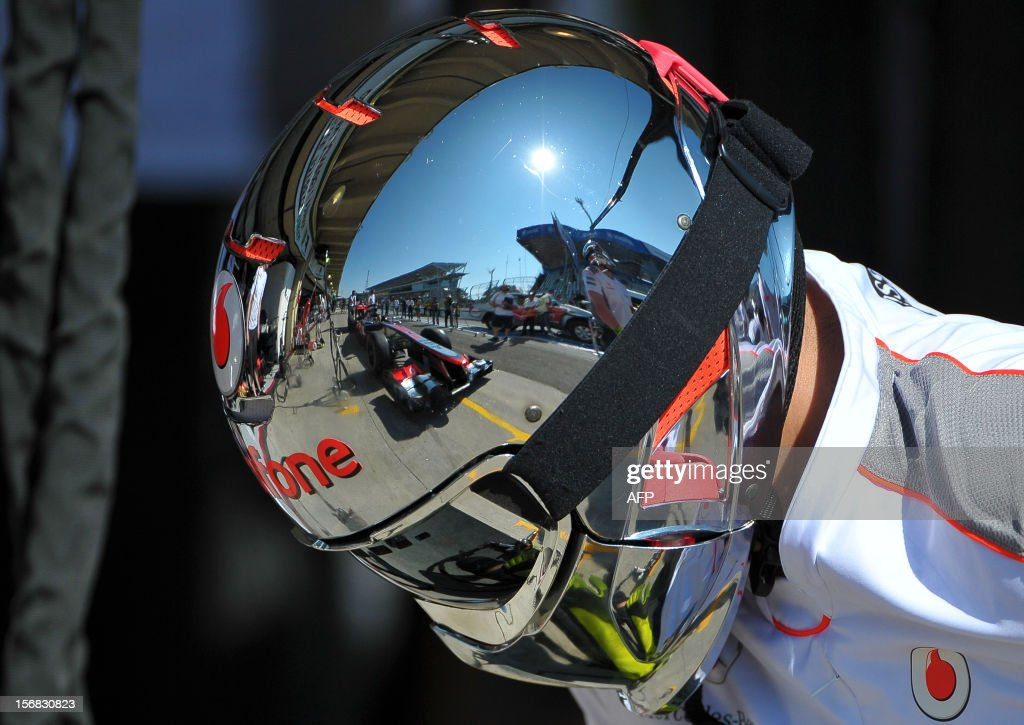 One of the cars of McLaren Formula One team is reflected on the helmet of a mechanic as he gets ready to change the tyres, at Interlagos motorsport circuit in Sao Paulo on November 22, 2012 ahead of the Brazilian Grand Prix this weekend.