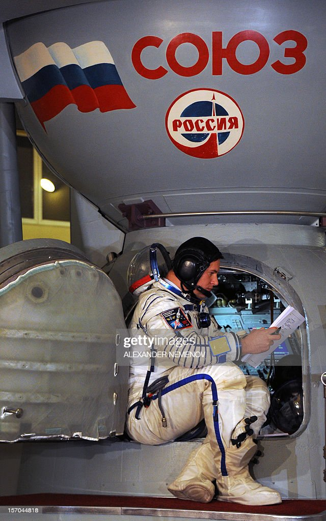 One of the crew members of the next expedition to the International Space Station Russian cosmonaut Roman Romanenko sits in the hatch of a mockup of...