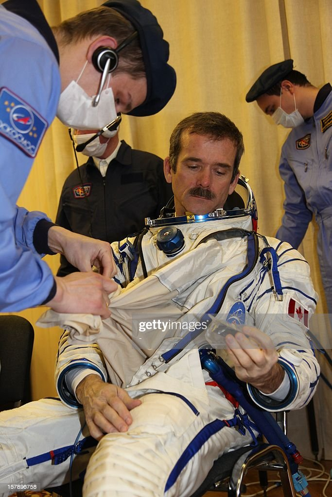One of the crew members of the next expedition to the International Space Station (ISS), Canadian astronaut Chris Hadfield, pust on his space suit during preflight preparation at the Russian leased Kazakhstan's Baikonur cosmodrome on December 7, 2012. Hadfield, Romanenko and Marshburn will join in December the remaining ISS crew, Russians Oleg Novitskiy and Evgeny Tarelkin, and Kevin Ford of the United States, who arrived there last month. AFP PHOTO / STR