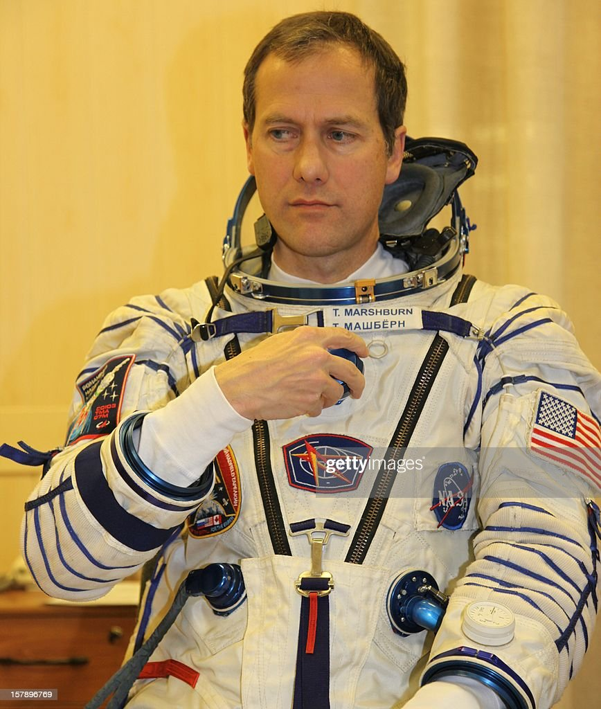 One of the crew members of the next expedition to the International Space Station (ISS), US astronaut Tom Marshburn, puts on his space suit during preflight preparation at the Russian leased Kazakhstan's Baikonur cosmodrome on December 7, 2012. Hadfield, Romanenko and Marshburn will join in December the remaining ISS crew, Russians Oleg Novitskiy and Evgeny Tarelkin, and Kevin Ford of the United States, who arrived there last month. AFP PHOTO / STR