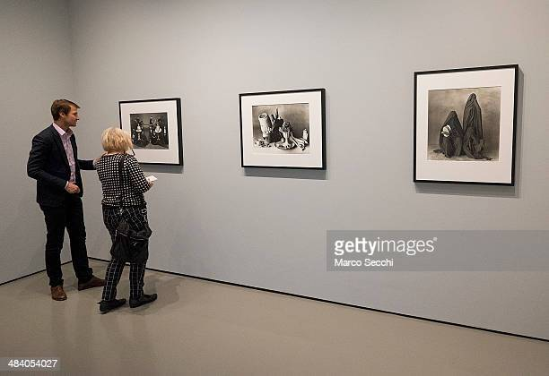 One of the Curators talks to a journalist in front of few photographs by Irving Penn during the press preview of the new exhibition at Palazzo Grassi...