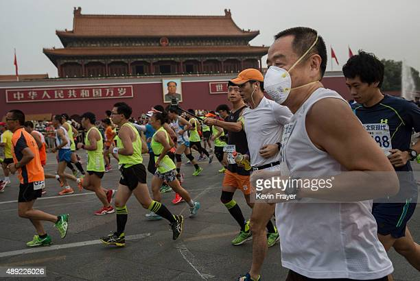 One of the few participants wearing a mask for pollution runs with others passed Tiananmen Gate while competing in the 2015 Beijing Marathon on a...