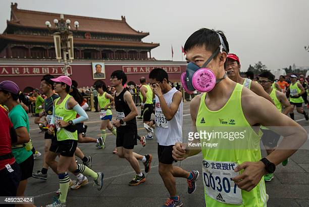 One of the few participants wearing a mask for pollution runs with others passed Tiananmen Gate while competing in the 2015 Beijing Marathon on...