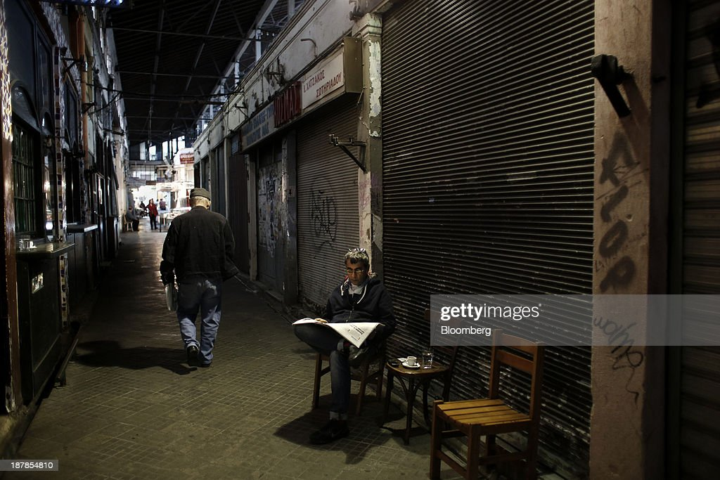 One of the few remaining store owners in Modiano district market sits and reads a newspaper outside his closed premises in Thessaloniki, Greece, on Wednesday, Nov. 13, 2013. Greece 'is following a fiscal adjustment program that aims to make the country's public finances sustainable on a permanent basis,' Finance Minister Yannis Stournaras told lawmakers during the debate, after holding talks with the troika earlier in the week. Photographer: Konstantinos Tsakalidis/Bloomberg via Getty Images