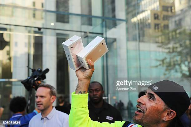 One of the first customers to buy a new iPhone walks out of an Apple store in Manhattan on September 16 2016 in New York City People around the globe...