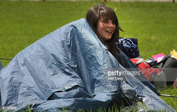 One of the first festival revellers attempts to set up her tent in the wind as she arrives at the Glastonbury Festival at Worthy Farm Pilton on June...