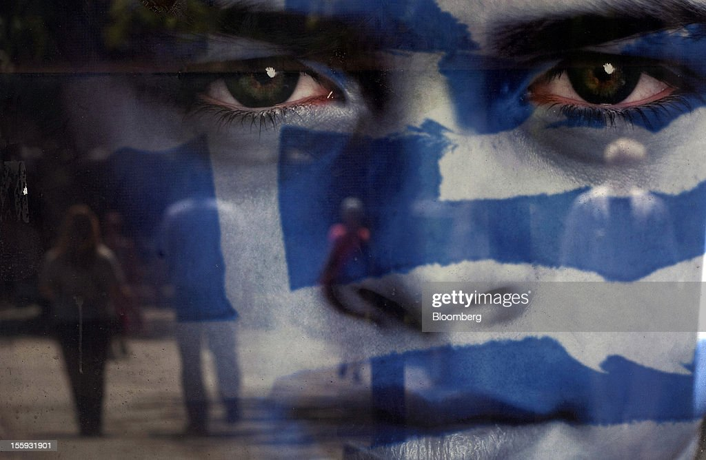 EDITORS' GUILD AWARDS 2012. One of the five photographs by Bloomberg photographer Simon Dawson shortlisted for the 'Bloomberg Business Photographer of the Year' category in the 2012 awards. Picture Shows: Pedestrians are reflected in a poster advertising the Greek national elections on the day of voting in Athens, Greece, on Sunday, May 6, 2012. Photographer: Simon Dawson/Bloomberg via Getty Images