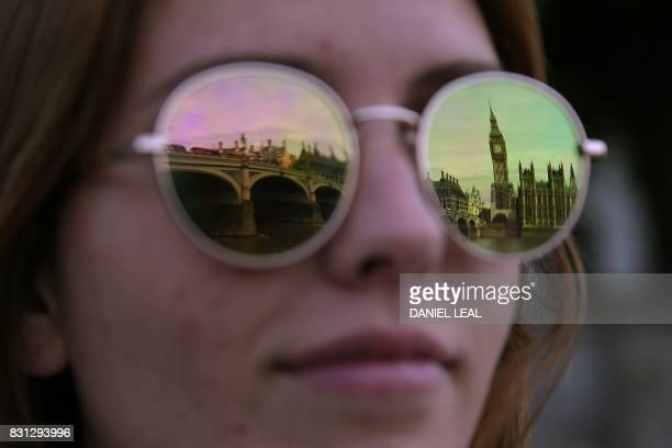 One of the four faces of the Great Clock of the Elizabeth Tower commonly referred to as Big Ben is reflected in the sunglasses of a Spanish tourist...