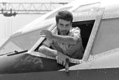 One of the hijackers of TWA Boeing 727 holding a gun emerging from the plane cockpit window 19 June 1985 at Beirut airport orders the newsmen to move...