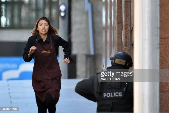 One of the hostages runs towards police from a cafe in the central business district of Sydney on December 15 2014 Five people ran out of a Sydney...