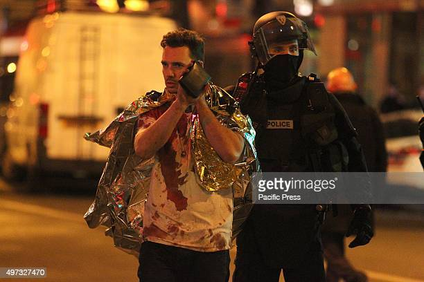 One of the injured victim escorted by the police in front Bataclan concert hall At least 129 people have been killed and over 200 injured 80 of which...