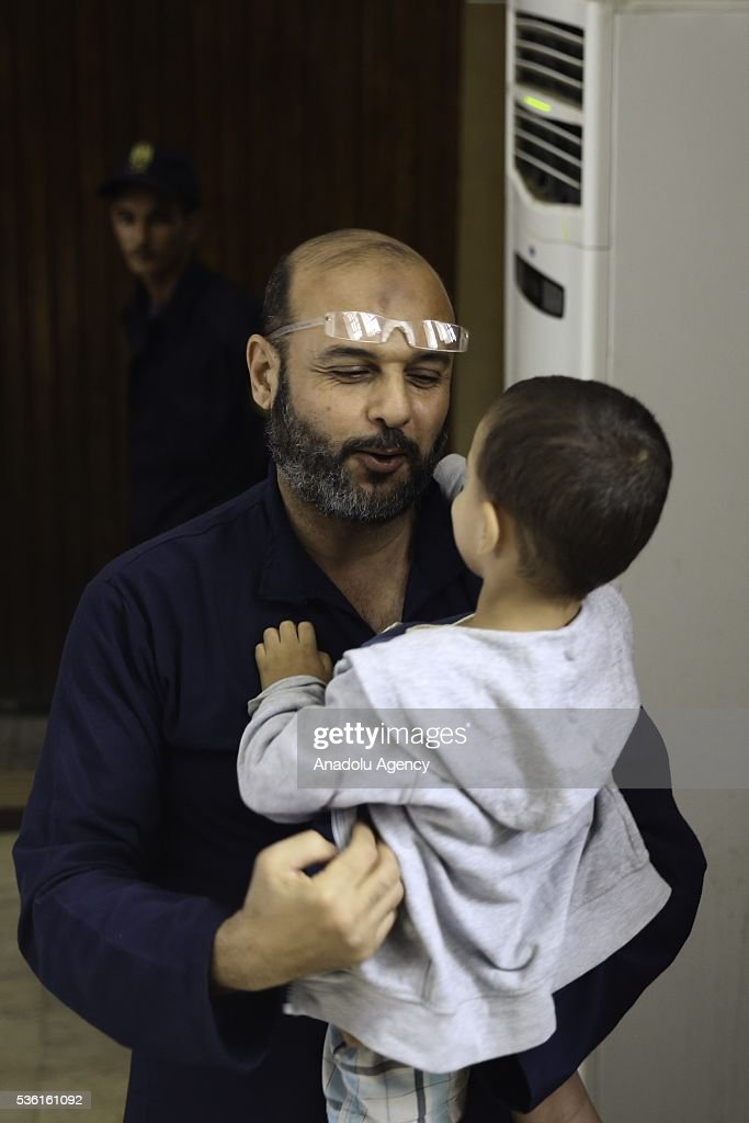 One of the leaders of the Muslim Brotherhood, Amr Zaki holds his son in his arms after he was given during the trials of Muslim Brotherhood members at the Police Academy in the capital Cairo, Egypt on May 31, 2016.