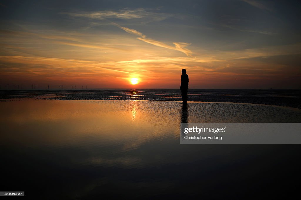 One of the life-size body cast statues of 'Another Place' created by the artist Antony Gormley looks out over the Mersey Estuary at sunset at Crosby beach on April 15, 2014 in Crosby, United Kingdom. Gormley today received his Knighthood from Queen Elizabeth II at Windsor Castle.