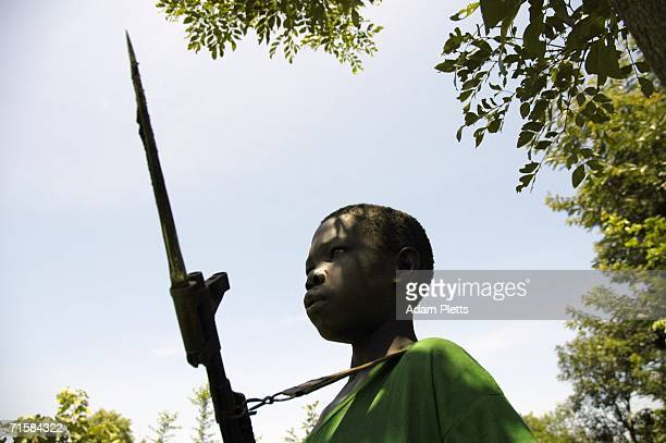 One of the many young boys who fight in the Lords Resistance Army stands guard as LRA leader Joseph Kony meets with the Southern Sudanese vice...