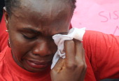 One of the mothers of the missing Chibok school girls wipes her tears as she cries during a rally by civil society groups pressing for the release of...