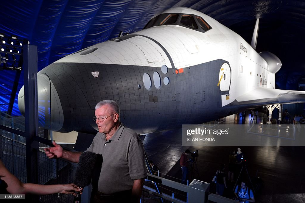 One of the original Enterprise pilots, astronaut Fred Haise, is interviewed as the Space Shuttle Enterprise is seen on display at the Intrepid Sea, Air & Space Museum's Space Shuttle Pavilion during a press preview July 18, 2012 in New York. The exhibit will officially open to the public July 19. AFP PHOTO/Stan HONDA