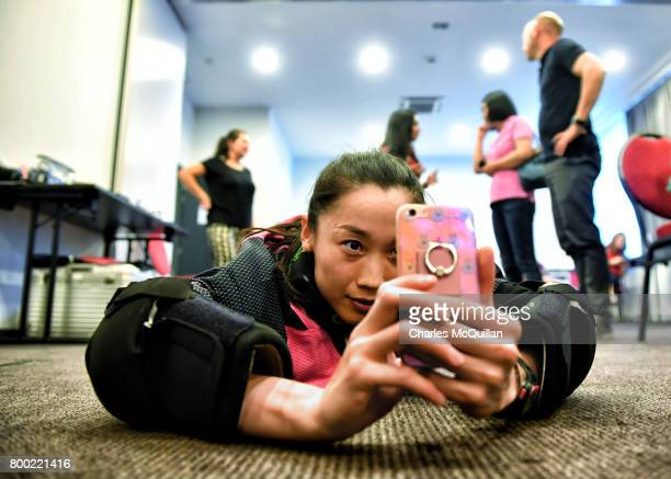 One of the participating team members takes a worm's eye view with her smartphone during a player portrait photo session for FINTRO Hockey World...