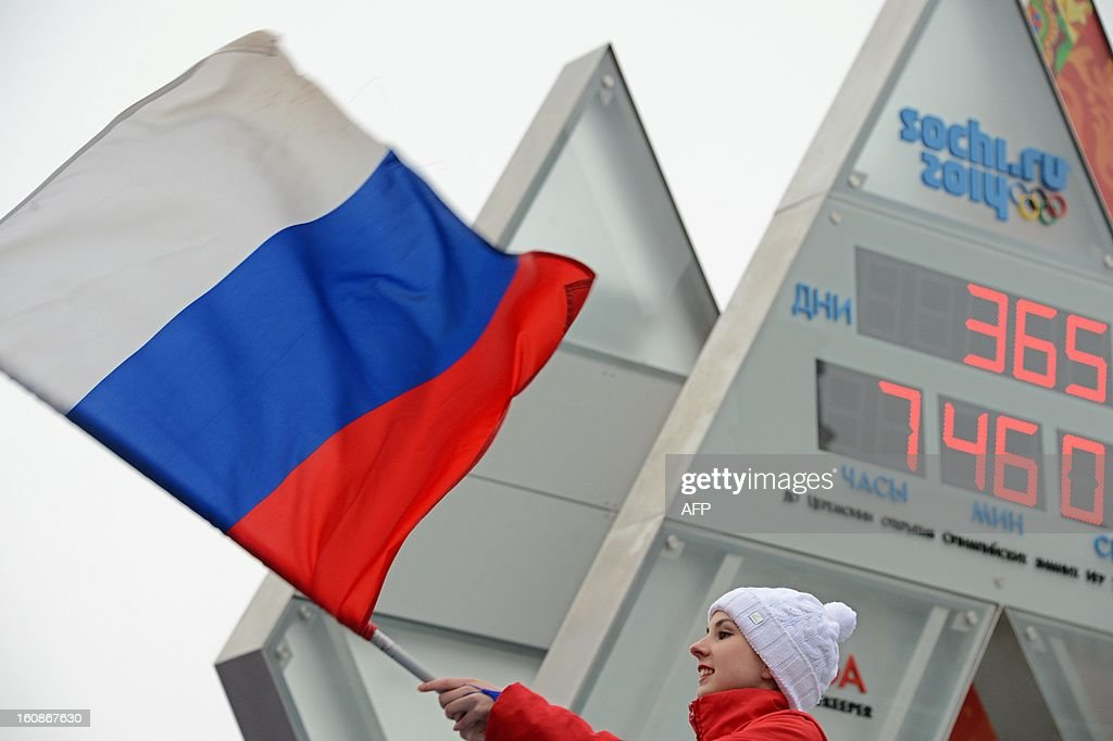 One of the performers waves a Russian flag near the Sochi 2014 countdown clock just outside the Kremlin in Moscow, on February 7, 2013, shortly after the clock unveiling. The clock screens display number of days (top) and time (hours, minutes, seconds) left to the opening of the Winter Olympics in Sochi.