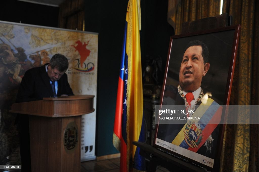 One of the Russian Communist politicians, Viktor Anpilov signs a condolence book near a portrait of late Venezuelan President Hugo Chavez at the Venezuela's embassy in Moscow on March 6, 2013. Russian President Vladimir Putin hailed today his late Venezuelan counterpart Hugo Chavez as an uncommon and strong man who had made a huge contribution to relations between Moscow and Caracas. Russia enjoys close military ties with Venezuela, which also represents one of the main oversees investment targets of the giant state oil company Rosneft.