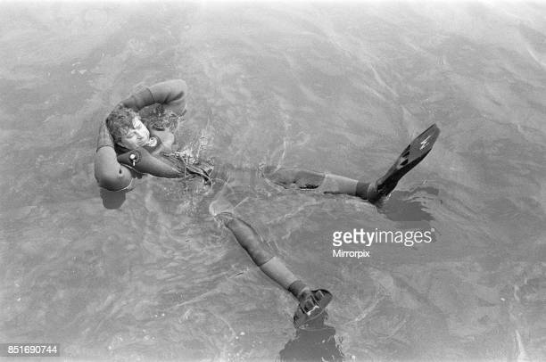 One of the salvage divers relaxes in the water close to the J Marr fishing trawler Navena after she was beached on Scarborough's south beach during a...