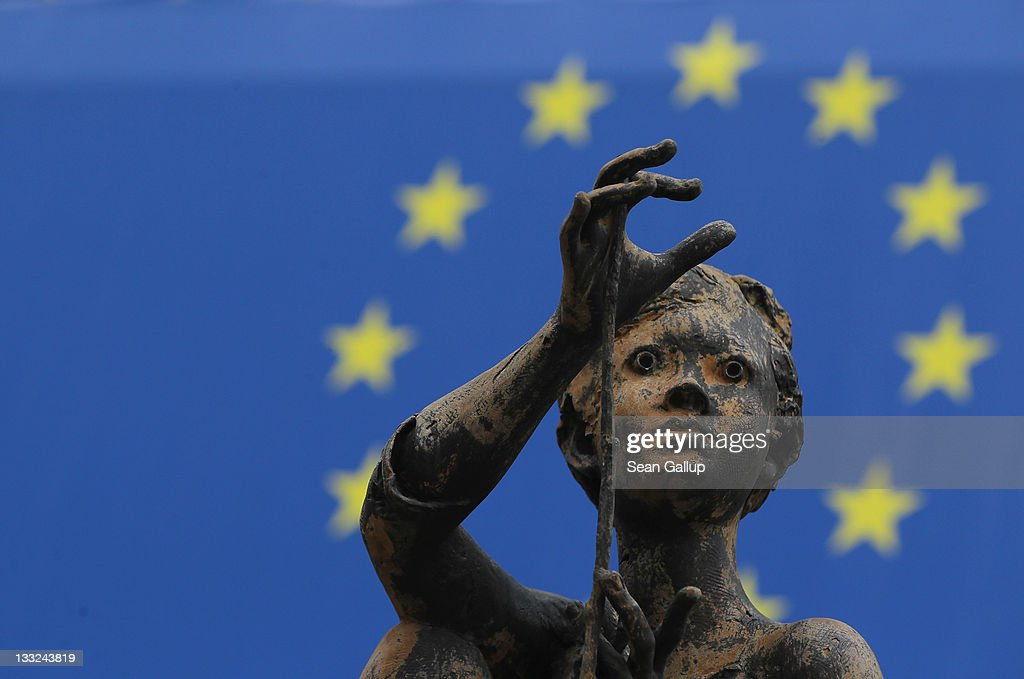 One of the sculptures of young girls by artist Rene Julien stands in front of a flag of the European Union at the Charlemagne building of the European Commission on November 17, 2011 in Brussels, Belgium. Eurozone member countries are continuing to struggle with a debt crisis afflicting a widening circle of nations as the rest of the world fears economic repurcussions.
