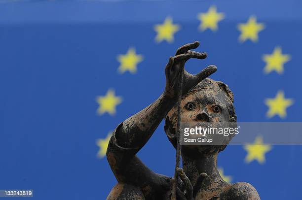One of the sculptures of young girls by artist Rene Julien stands in front of a flag of the European Union at the Charlemagne building of the...