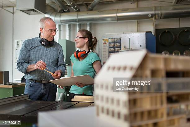 One of the students in conversation with her tutor in the model making department department seen here in a woodwork room at the Beuth technical...