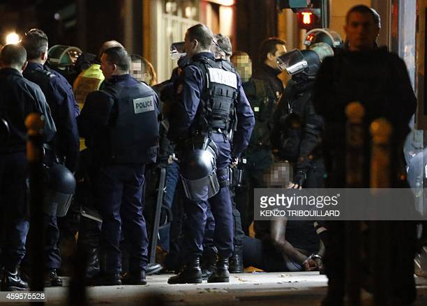 One of the two alleged robbers who targeted a Cartier jewellery store on the ChampsElysees sits on the ground after surrendering to French police...
