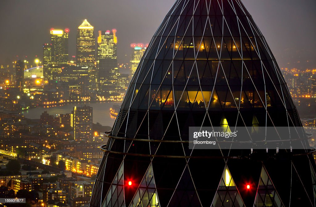 EDITORS' GUILD AWARDS 2012. One of the winning set of five photographs for the 'Bloomberg Business Photographer of the Year' by photographer Jason Alden. Picture Shows: The Swiss Re Insurance building, also known as 'the Gherkin', foreground, and the towers of the Canary Wharf business district are seen against the city skyline in London, U.K. on Thursday, July 12, 2012. Photographer: Jason Alden/Bloomberg via Getty Images