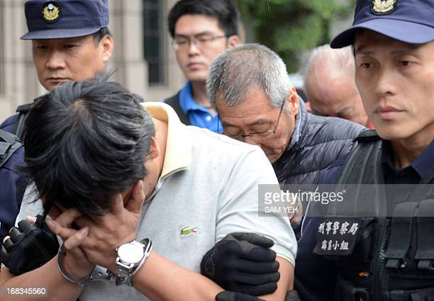 One of three drug smuggling suspects is escorted by police at the Criminal Investigation Bureau after a press conference in Taipei on May 9 2013...