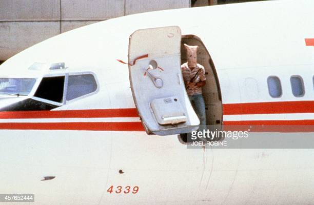 One of two heavilyarmed Lebanese Shiite militants his face hidden with a bag who hijacked a TWA passenger Boeing 727 aircraft looks out from the door...