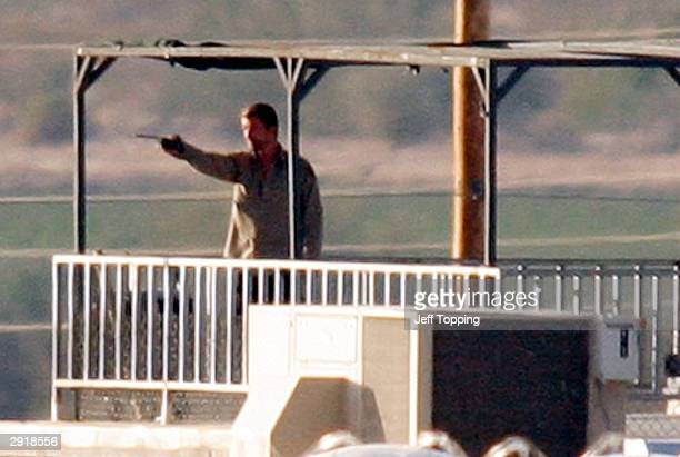 One of two inmates holding a hostage at the State Prison ComplexLewis points a walkietalkie on the observation deck of a guard tower wearing a...