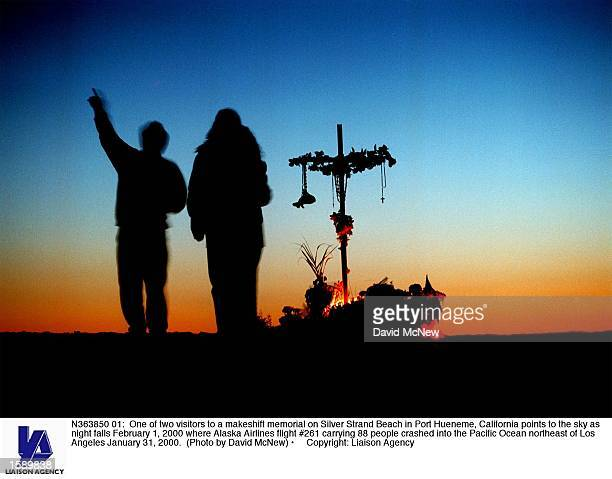 One of two visitors to a makeshift memorial on Silver Strand Beach in Port Hueneme California points to the sky as night falls February 1 2000 where...