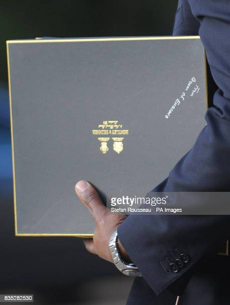 One of US President Obama's staff carries a gift from the Queen to his car at Buckingham Palace today where he had a private audience with Her...
