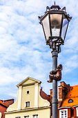 One of Wroclaw's famous little bronze gnomes dwarfs or krasnale statuettes climbing a streetlight in the old town market square