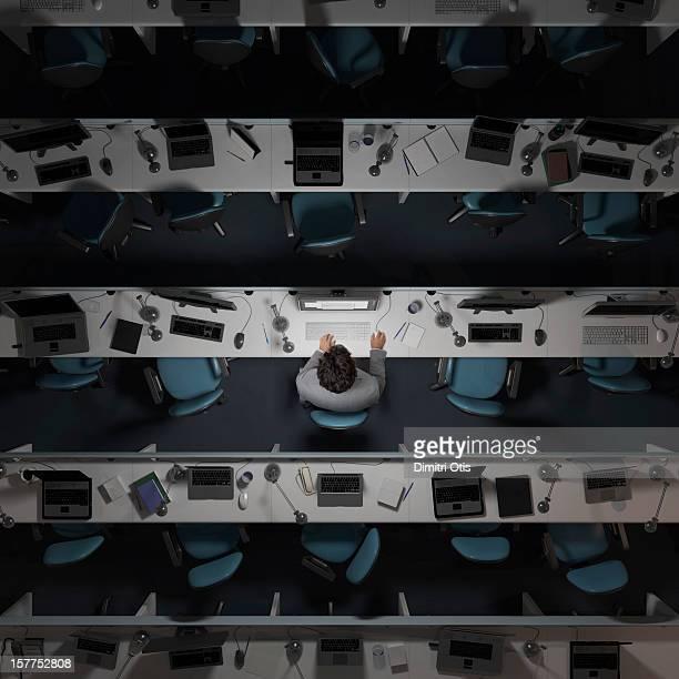 One office worker working in an empty, dark office