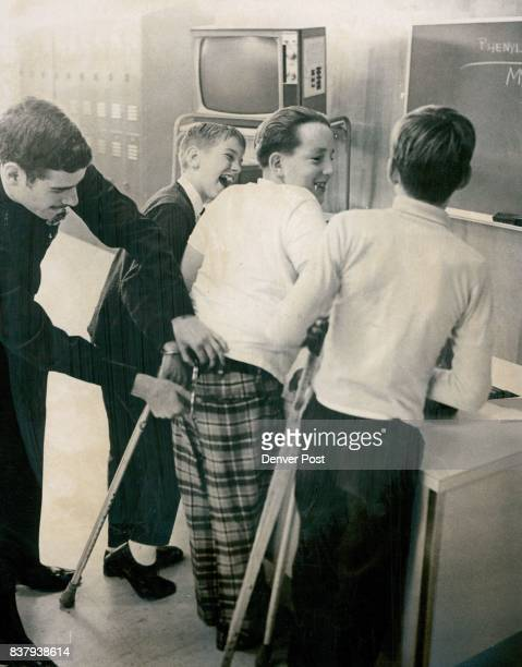 One officer can handcuff three persons at once looping cuffs through belt of the man in the middle as Patrolman B L Segall demonstrates to 'suspects'...