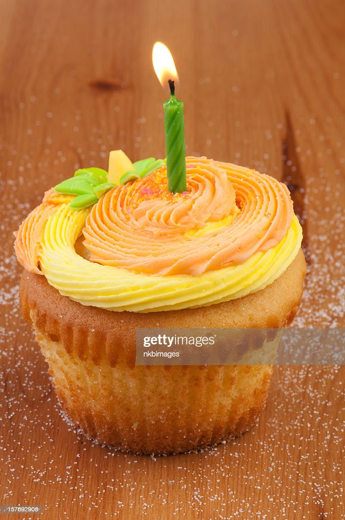 One orange and yellow decorated cupcake with burning candle : Stock Photo