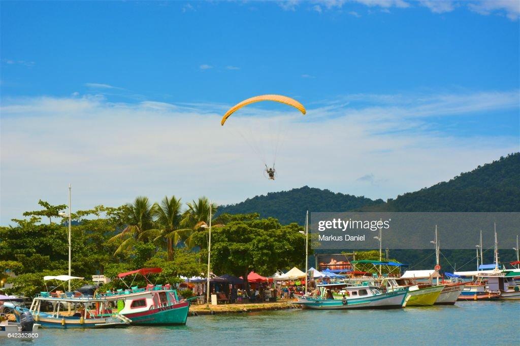 One paraglider over the main pier in Paraty, Rio de Janeiro : Stock Photo