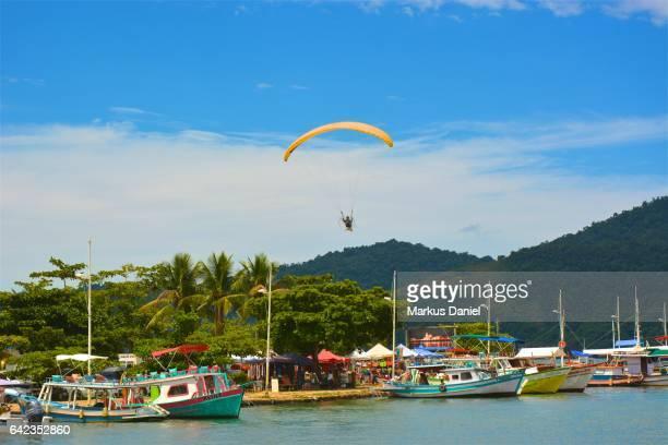 One paraglider over the main pier in Paraty, Rio de Janeiro